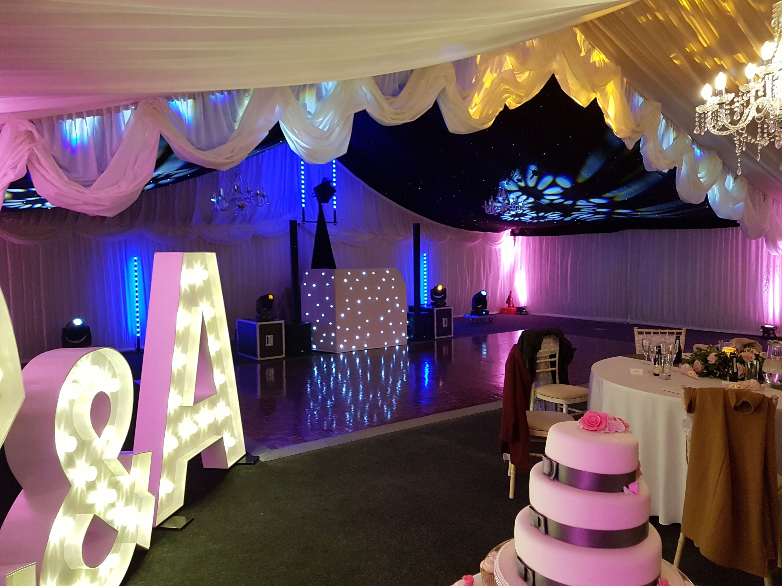 Mobile disco with white DJ booth, large lettters and cake