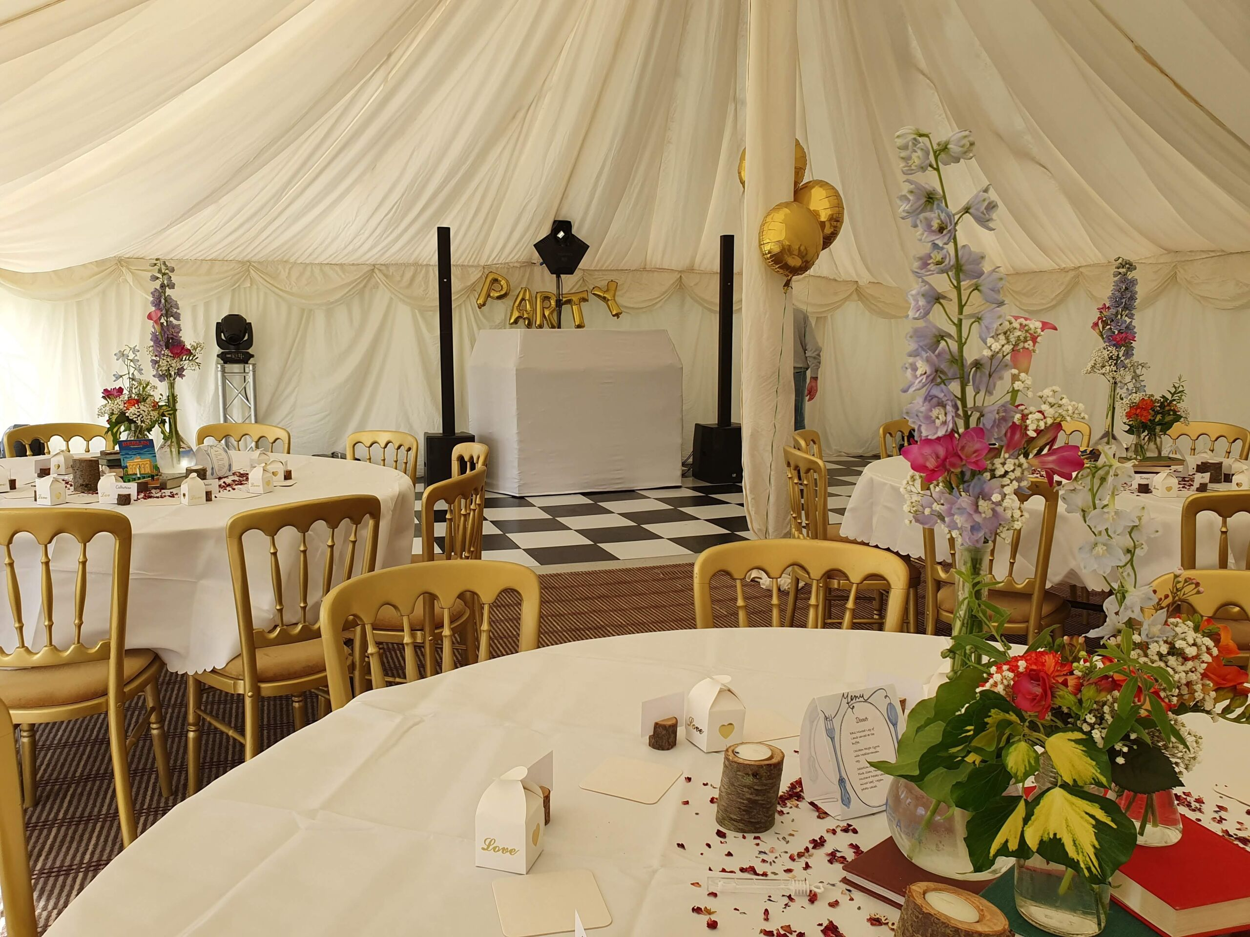 Wedding disco set up in a marquee with chequerboard dance floor