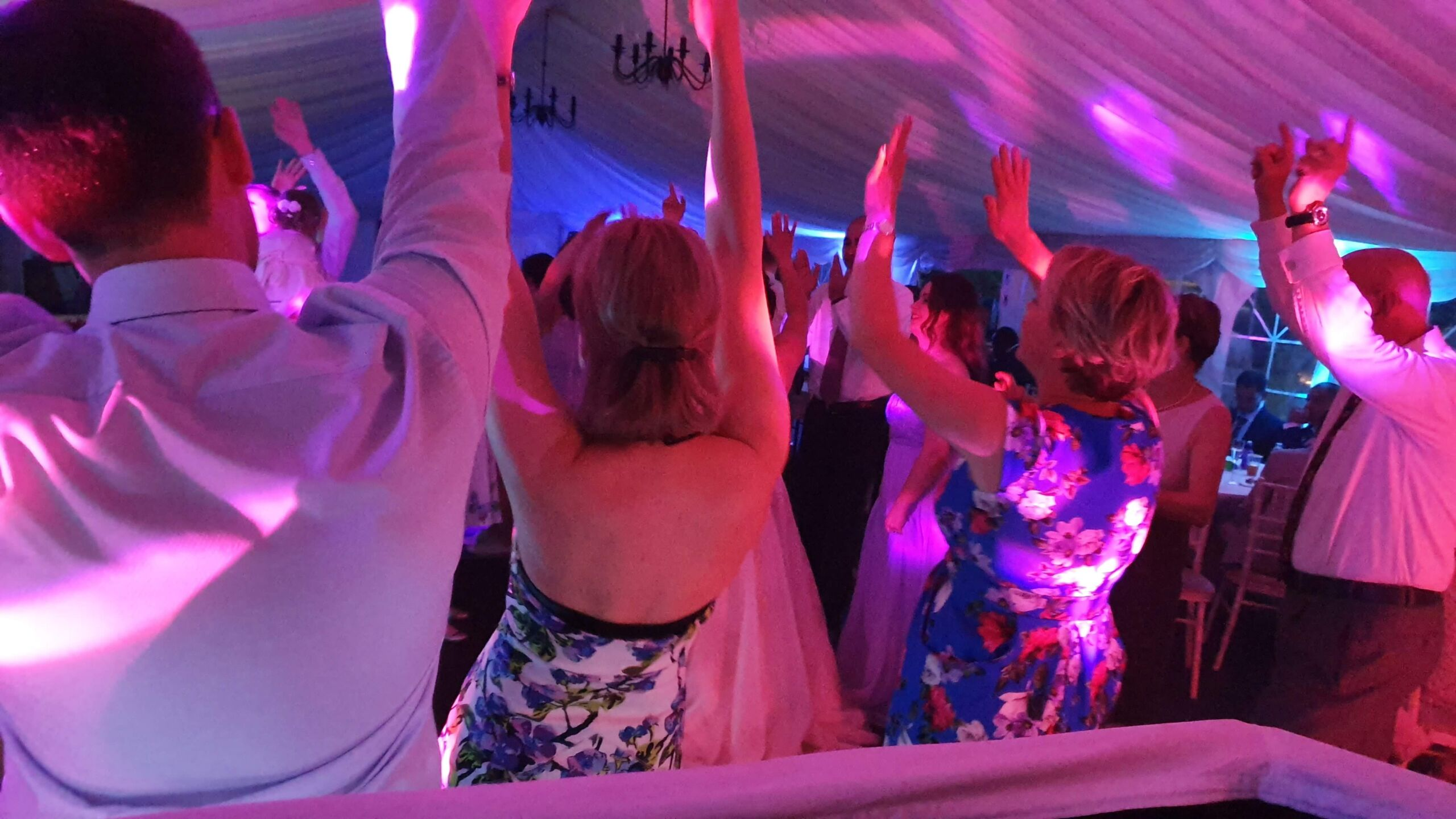 Dancers with hands in the air at a wedding
